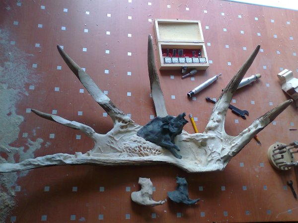 Phase 3 - The first figure, a laika, is roughed out in wood and further detail of trees and bushes are added to the moose antler background. (Dmitry Gorodetsky mixed media moose antler sculpture, in progress)