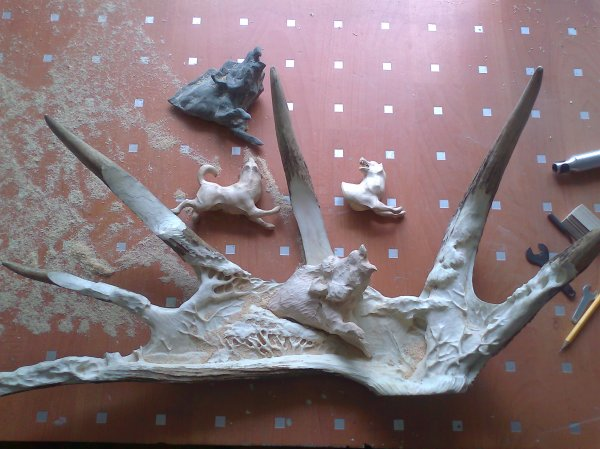 Phase 4 - The two laikas are refined and the wild boar is roughed out in wood. Further detail of trees and bushes are added to the moose antler background. (Dmitry Gorodetsky mixed media moose antler sculpture, in progress)